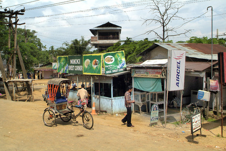 poorness: Assam, India - September 30th, 2007: Unidentified indian inhabitants, rickshaw and different shops in a small village on the main road between Bhutan and Gauharti Editorial