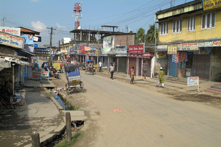 poorness: Assam, India - October 30: Unidentified people in a dusty and poorly shopping street in a small village unknown on the main road between Bhutan and Gauharti city in the northern part of Assam Editorial
