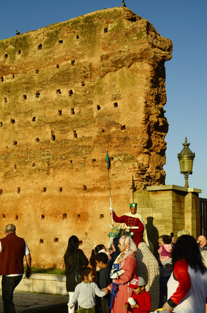 18th: Rabat, Morocco - November 18th 2014: Unidentified honor guard in traditional uniform on horse and tourists on entrance to mausoleum Mohammed V and Hassan tower with part of the old wall
