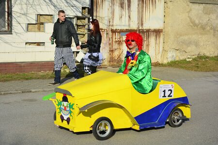 february 14th: Reisenberg, Austria - February 14th 2015: Unidentified discuised people by traditional carnival revelry in the tiny village in Lower Austria, clown in funny vehicle