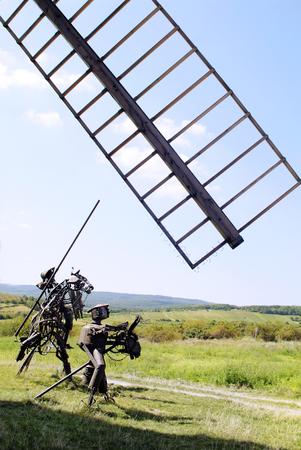 don quijote: Retz, Austria - 06 de septiembre 2005: Escultura con el legendario Don Quijote y Sancho Panza hechas de material de desecho de hierro viejo y vela molino de viento
