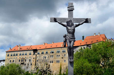 krumlov: Cesky Krumlov, Czech Republic, thunderclouds and cross with Christ and part of castle Krumlov in the Unesco World Heritage site in Bohemia