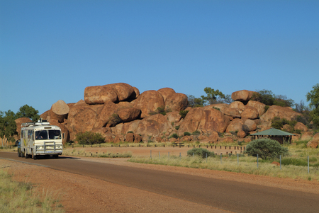 natural landmark: Tennant Creek, Australia- April 20 th 2010: Private bus and touristst by impressive Devils Marbles rock formation, a natural landmark and tourist attraction in Northern Territory Editorial