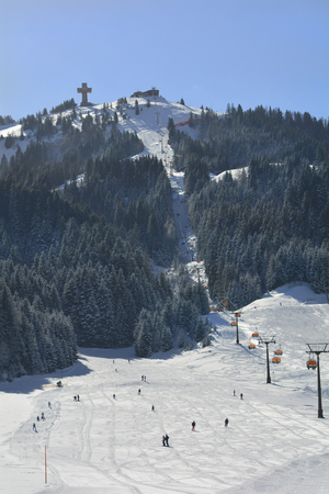 station ski: St. Jakob, Austria - March 3rd 2015: Unidentified people on ski slope and chair lift to summit station Buchensteinwand with accesibleJakobs-cross in Pillersee valley Editorial