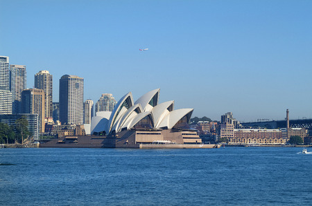 Sydney, Australia - May 10th 2010: Impressive Sydney Opera building, office buildings and hotels behind and The Rocks on right side