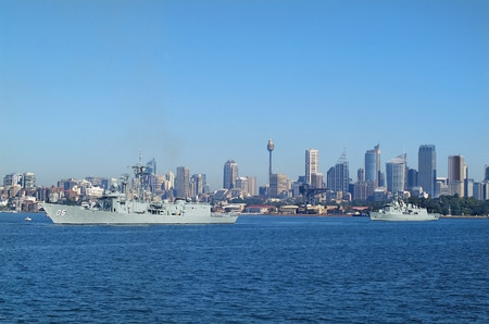 Sydney, Australia - May 10th 2010: Worships of Australian navy in Port Jackson, buildings and Centrepoint tower aka Sydney tower in background Editorial