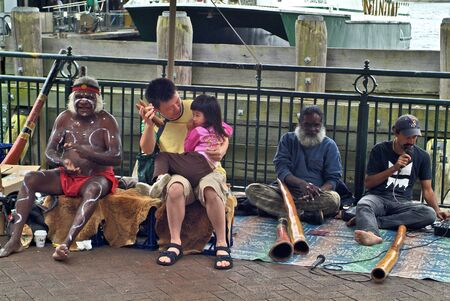 Sydney, Australia - February 8th 2008: Unidentified Aborigines with body painting and traditional didgeridoos, Asian tourist  with daughter on Circular Quay
