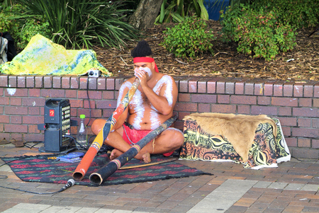 Sydney, Australia - February 8th 2008: Unidentified Aborigine with body painting, didgeridoo and modern equipment playing traditional music on Circular Quay