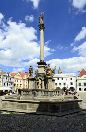 unesco in czech republic: Cesky Krumlov, Czechia - August 11th 2013: Unidentified tourists, restaurants, fountain with plague column and buildings around the market square in the Unesco World Heritage site in Bohemia Editorial