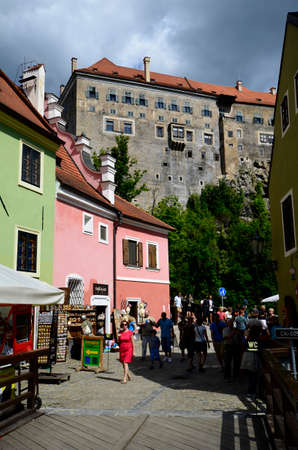unesco in czech republic: Cesky Krumlov, Czechia - August 11th 2013: Unidentified tourists on small street with shops and colourful homes, part of the castle above in the Unesco World Heritage site in Bohemia