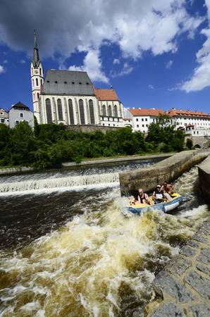 watersport: Cesky Krumlov, Czechia - August 11th 2013: Unidentified people in rubber raft on Moldau (Vlatava) river with church of Saint Vitus in the Unesco World Heritage site in Bohemia, rafting on river Vlatava (Moldau) is a preferred watersport in this area