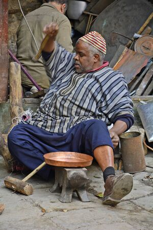 fes: Fes, Morocco - November 20th 2014: Unidentified man producing brass articles on place es-Seffarine in souk Fes el-Bali, place for brassware workers