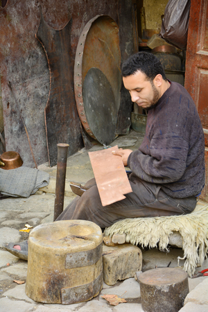 articles: Fes, Morocco - November 20th 2014: Unidentified man producing brass articles on place es-Seffarine in souk Fes el-Bali, place for brassware workers
