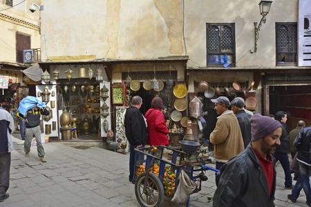 street vendor: Fes, Morocco - November 20th 2014: Unidentified people on Seffarine in Fes el-Bali souk, street vendor with wheelbarrow