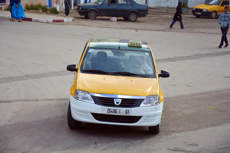 petit: Beni Mellal, Morocco - November 23rd 2014: Unidentified people and Petit taxi - typical mode of transport up to four people and with different colors in every city