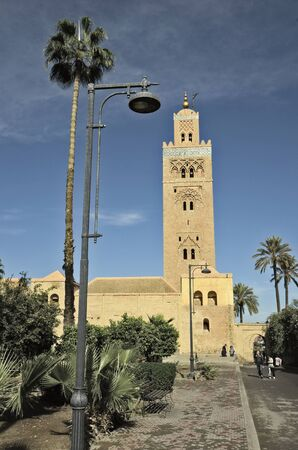 people in the street: Marrakesh, Morocco - November 23rd 2014: Unidentified people, street lamp and Koutoubia mosque Editorial