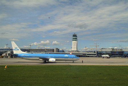 klm: Schwechat, Austria - May 20th 2006: KLM aircraft Boeing 737 on runway of Vienna airport with new tower behind Editorial