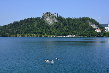 recreation area: Bled, Slovenia - July 7th 2015: Unidentified people swimming in lake bled with castle above, preferred tourist attraction and recreation area Editorial