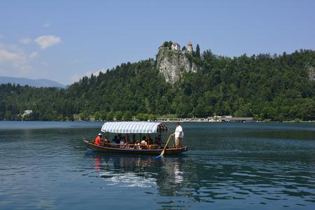 Bled, Slowenien - 7. Juli 2015: Unidentified Touristen in Ruderboot auf dem See benannt Pletna oben entlüftet mit Schloss, bevorzugte Verkehrsmittel auf See