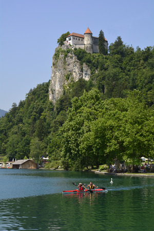 bled: Bled, Slovenia - July 7th 2015: Unidentified people in kayak on lake bled with castle above and promenade with swimming area