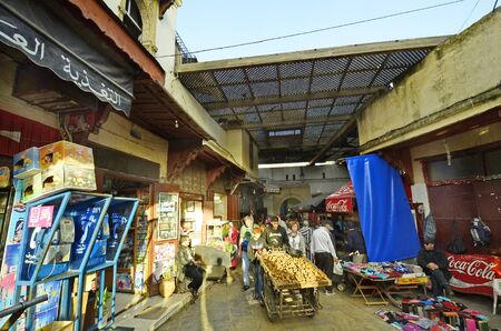 street vendor: Fes, Morocco - November 20th 2014: unidentified people and street vendor with wheel barrow in souk fes el-Bali, traditional shopping mall