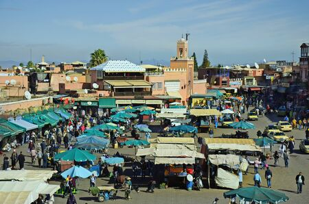 tourist attraction: Marrakesh, Morocco - November 23rd 2014: Unidentified people, kiosks, shops and market stalls on Djemaa el-Fna square, a preferred tourist attraction and Unesco world heritage site Editorial