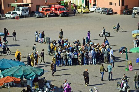 preferred: Marrakesh, Morocco - November 23rd 2014: Unidentified people on Djemaa el-Fna watching street performe, Unesco world heritage site and preferred place for tourists and inhabitants