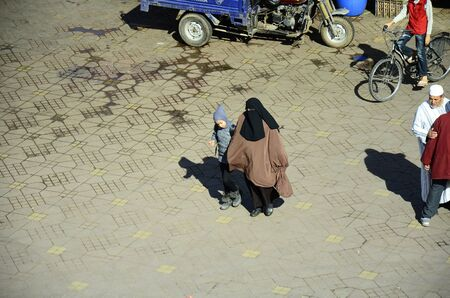 veiled: Marrakesh, Morocco - November 23rd 2014: Unidentified people and woman fully veiled on Djemaa el-Fna square