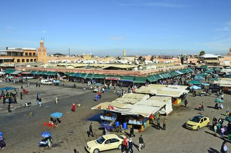 preferred: Marrakesh, Morocco - November 23rd 2014: Unidentified people, kiosks, shops and market stalls on Djemaa el-Fna square, a preferred tourist attraction and Unesco world heritage site Editorial