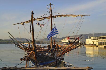 Volos, Griekenland - 2 oktober 2012: Nostalgische roeiboot - kombuis in de haven van Volos, op de achtergrond de auto ferry naar de Griekse eilanden