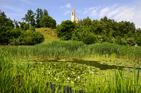 constantino: Italy, pond with water lilies and church San Constantino in Siusi Siusi allo Sciliar