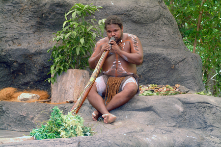 Kuranda, Australia - March 1st 2005: unidentified aborigene with body painting playing traditional didgeridoo instrument Editorial