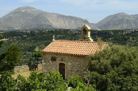 Greece, Crete, chapel for apostles petrus and paulus with bell tower and wind wheel on mountain top Stock Photo