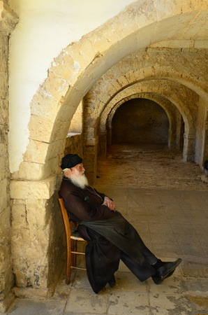 Arkadi, Greece, May 25th 2014: Unidentified Monk in the arcades of Arkadi monastery, a sanctuary Natonal in Crete,