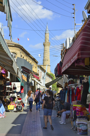 selimiye mosque: Nicosia, Cyprus - October 20th 2015: Unidentified people in small streets of the pedestrian precinct with different shops and minaret of Selimiye mosque in background Editorial