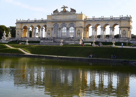 the gloriette: Vienna, Austria - September 17th 2012: Tourist attraction Gloriette with reflection in the pond, building in the Schoenbrunn garden is now a cafe and viewing point