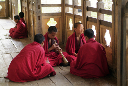 schoolboys: Ngatsang, Bhutan - September 28th 2007: Unidentified young monks as schoolboys in Ngamthrang Gompa playing trumpet nemad Rgya-Gling
