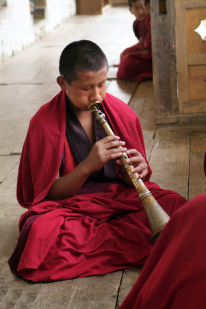 gompa: Ngatsang, Bhutan - September 28th 2007: Unidentified young monk playing trumpet named Rgya-Gling in Ngamthrang Gompa