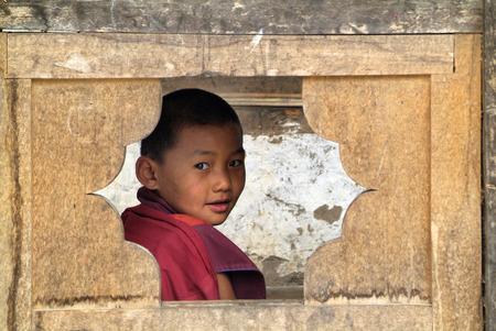 gompa: Ngatsang, Bhutan - September 28th 2007: Unidentified young monk looking through window in Ngamthrang Gompa Editorial