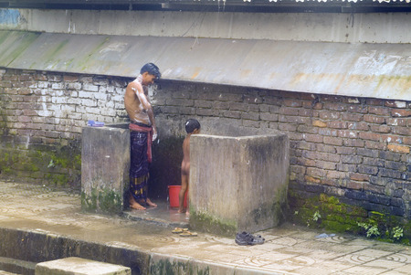 a bathing place: Dhaka, Bangladesh - September 17th 2007: Unidentified man and child on public bathing place in the city