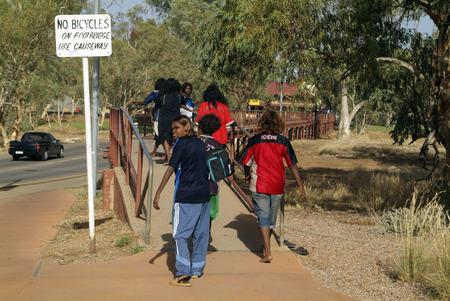 aborigines: Alice Springs, Australia - February 29th 2008: Unidentified aborigines youth on way to school crossing bridge over dry Todd river Editorial