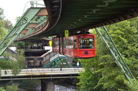 mode transport: Wuppertal, Germany - May 27th 2011: public overhead monorail on track leaving a train station, traditional mode of transport