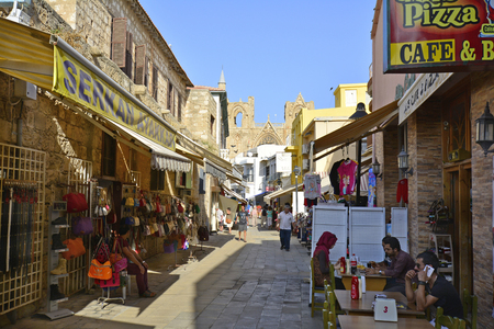 Famagusta, Cyprus - October 16th 2015: Unidentified people in shopping street with different restaurants and shops, Lala Mustafa Pasha mosque in background