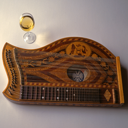 zither with old Austrian emblem and glass of wine - remembrance to movie The Third Man and music from Anton Karas Editorial