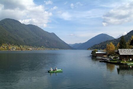 rowing boat: Weissensee, Austria - October 9th 2007: Unidentified people in rowing boat on lake