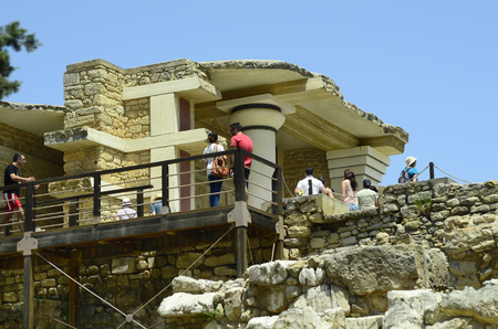 tourist attraction: Knossos, Greece - May 26th 2014: Unidentified tourists by sightseeing of the ancient Minoan palace in Crete, a tourist attraction and archeological site of bronce age