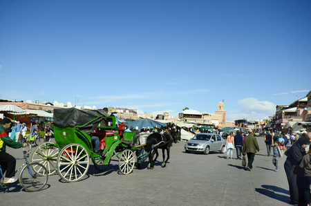 horse drawn: Marrakesh, Morocco - November 22nd 2014: Unidentified people and horse drawn coach on Djemaa Elfna, tourist attraction and UNESCO World Heritage Site