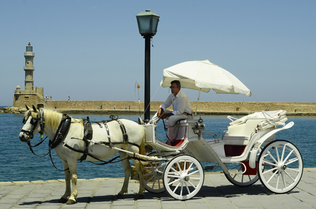 coachman: Chania, Greece - May 27th 2014: Unidentified people and horse drawn coach in front of  Venetian lighthouse in the harbor of the medieval village in Crete