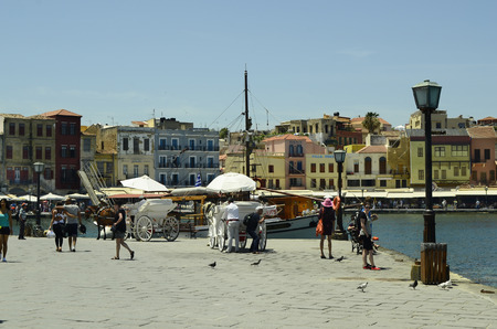 the coachman: Chania, Greece - May 27th 2014: Unidentified people, horse drawn coach and different restaurants, shops and hotels along the harbor of the medieval village in Crete