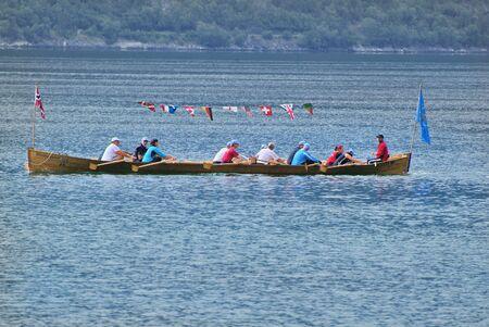 Kaupanger, Noorwegen - 13 juni 2009: De niet geïdentificeerde mensen in de roeiboot met verschillende vlaggen op Sognefjord